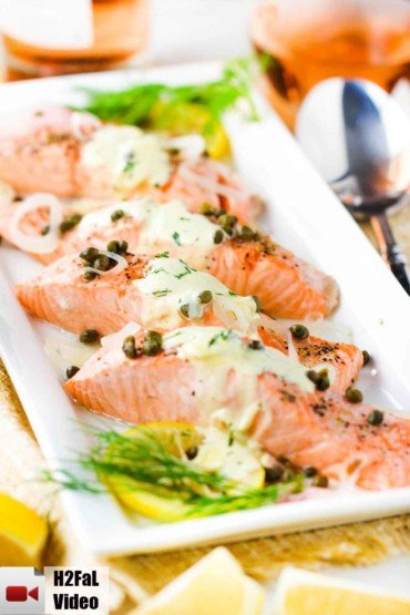 Poached salmon with capers and hollandaise sauce on a white platter