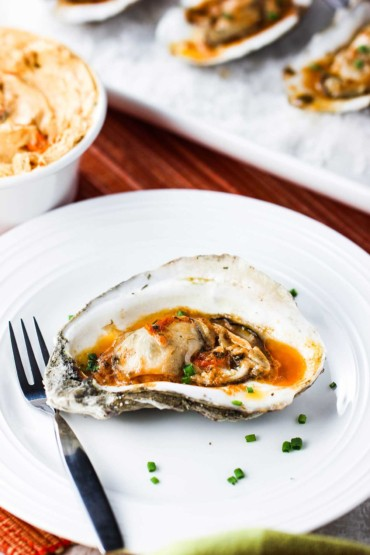 Grilled Oysters with Roasted Tomato Butter on a plate with rock salt