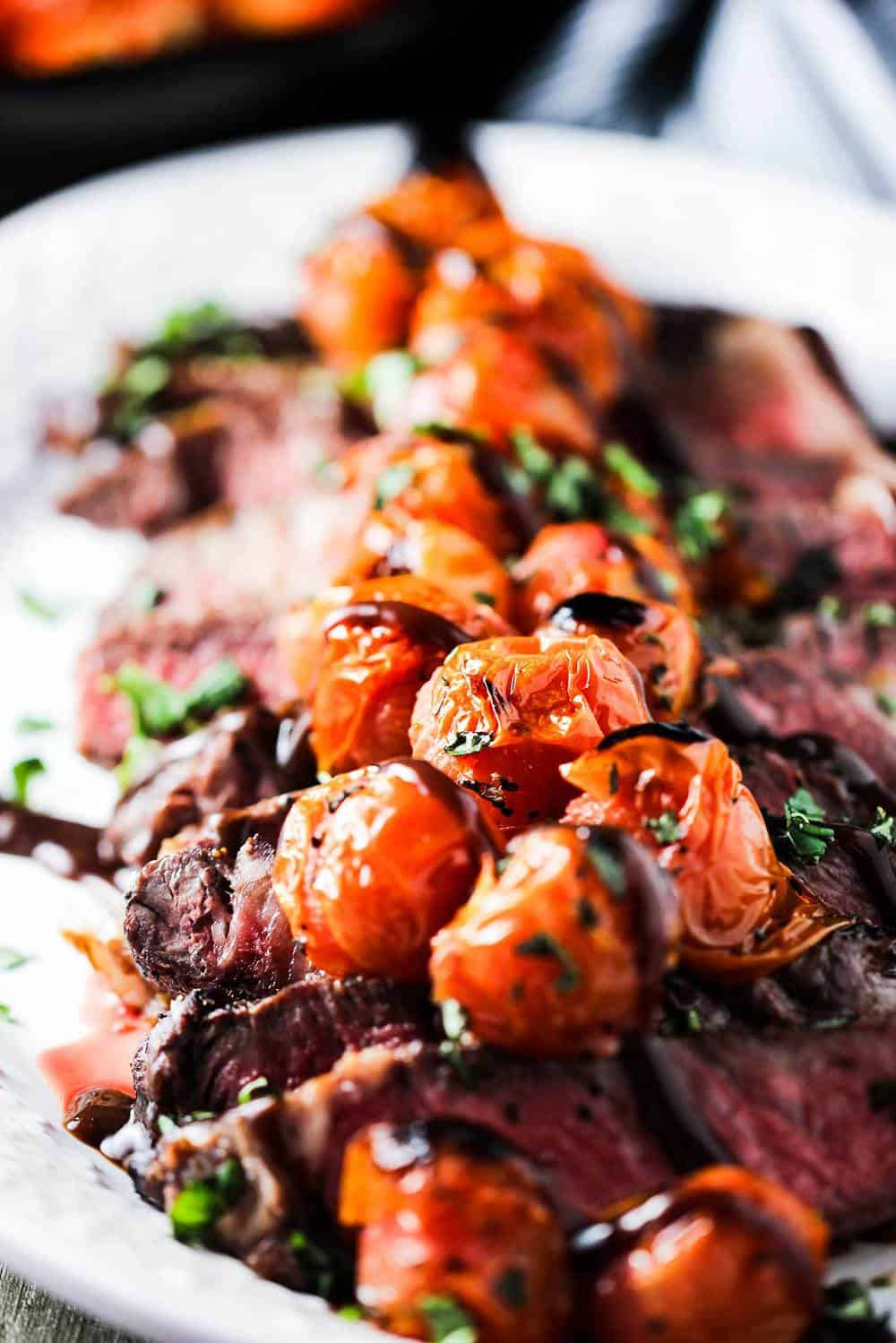 Seared ribeye with blistered tomatoes and bordelaise sauce on a platter