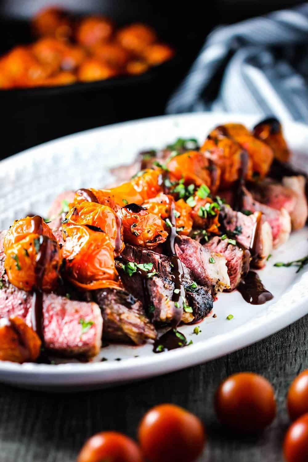 A white platter of seared ribeye with blistered tomatoes and bordelaise sauce on top