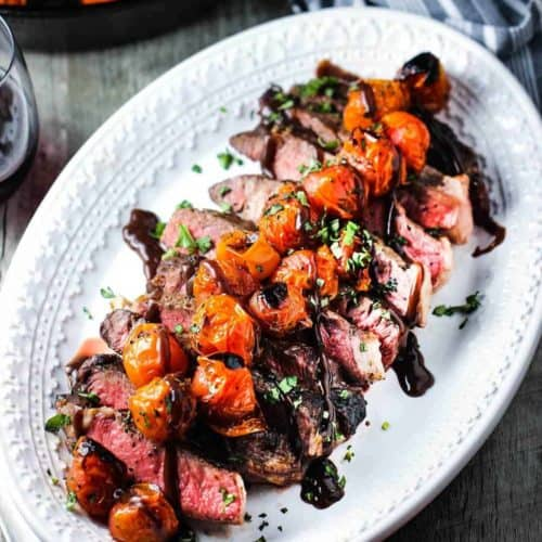 Sliced ribeye steak on a platter with roasted tomatoes and borderalaise sauce