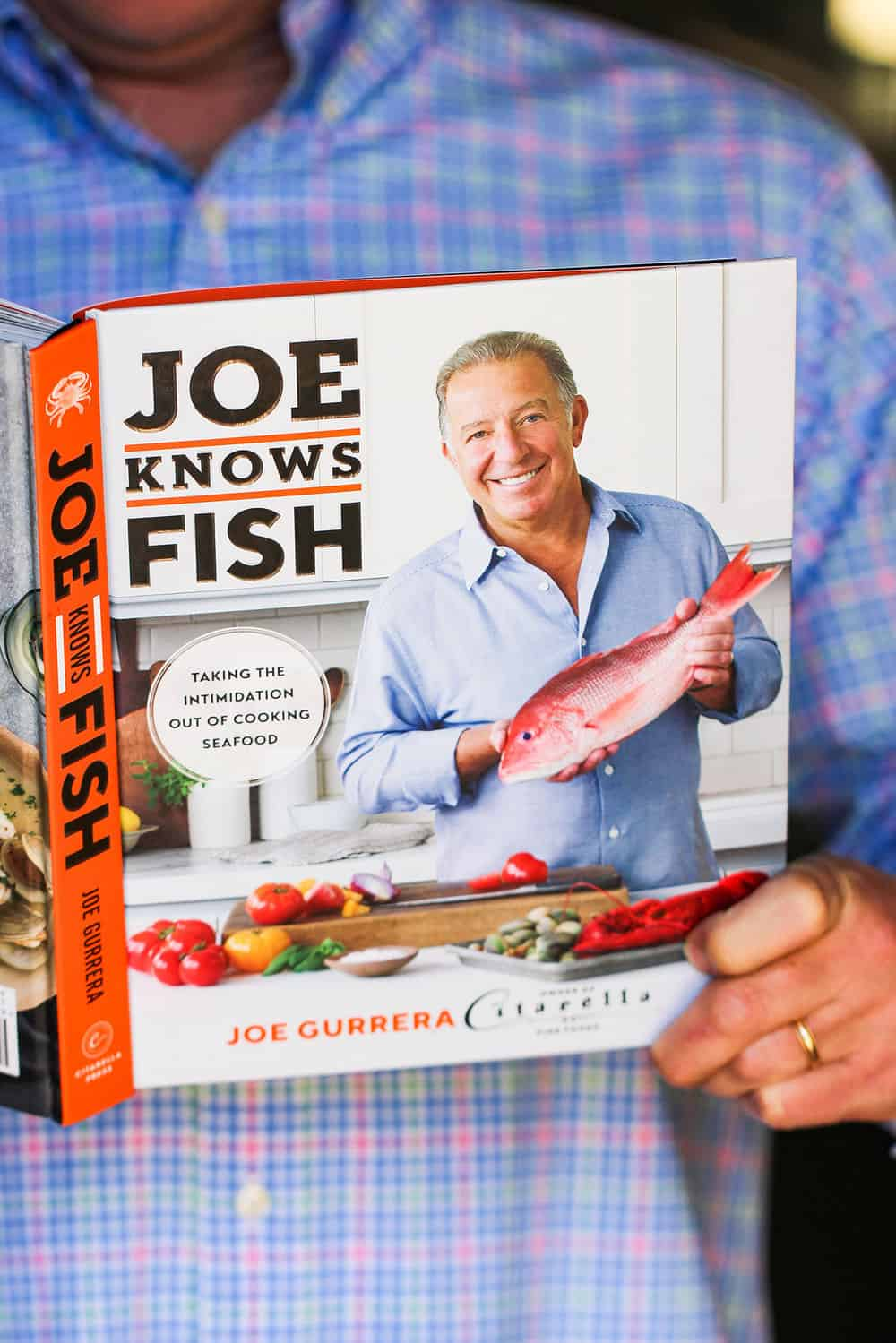 "A male in a blue shirt hold the cookbook ""Joe Knows Fish."""