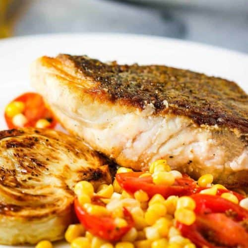 Sautéed Wild Striped Bass on a white plate with corn tomato salad and roasted fennel.