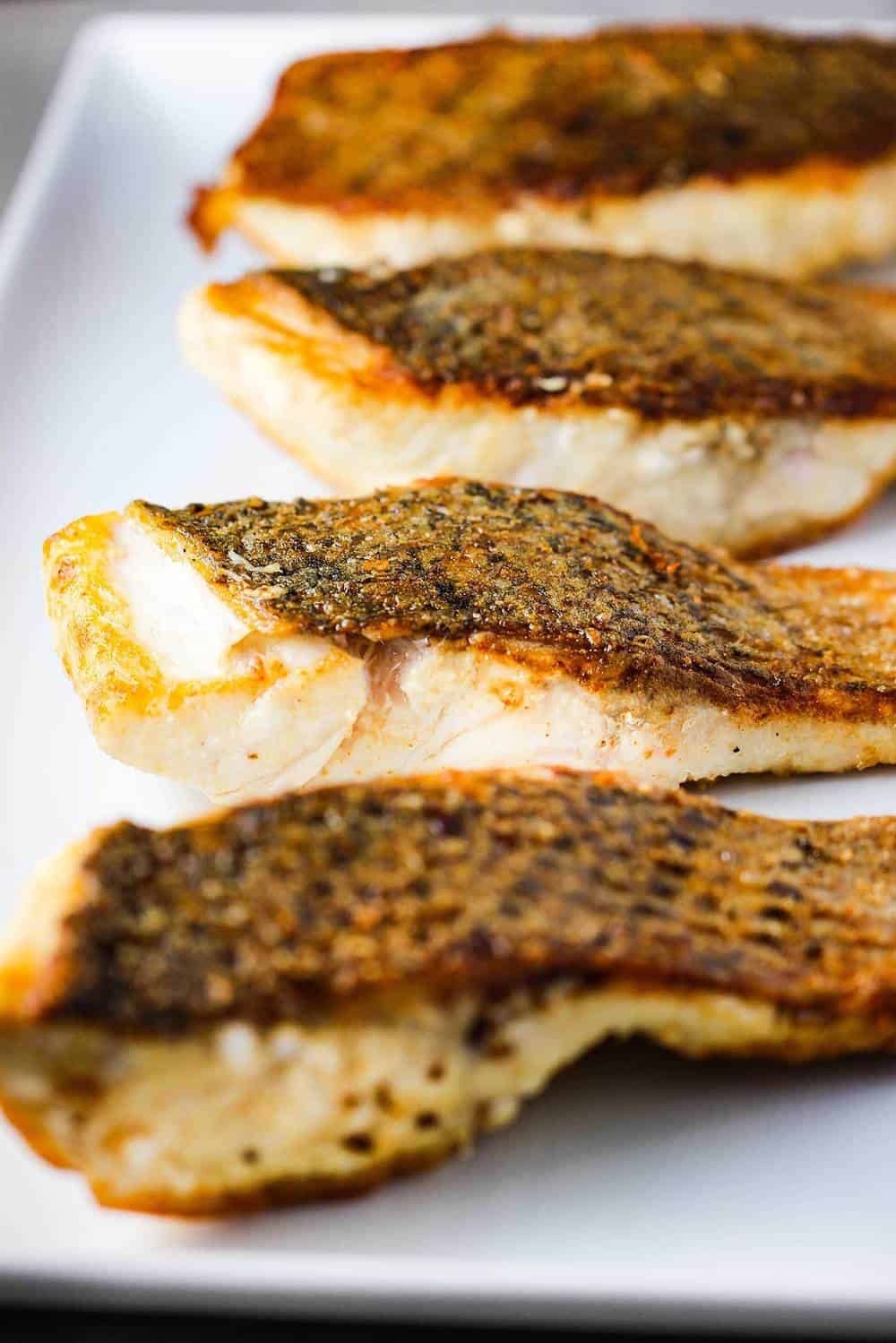 A large white platter holding four sautéed wild striped bass fillets