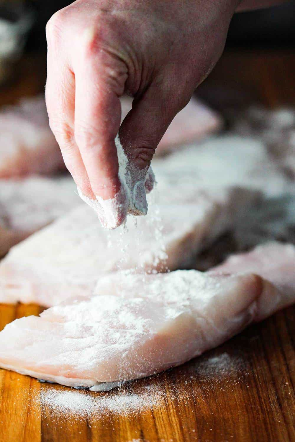 Fingers dusting flour over fresh wild striped bass fillets