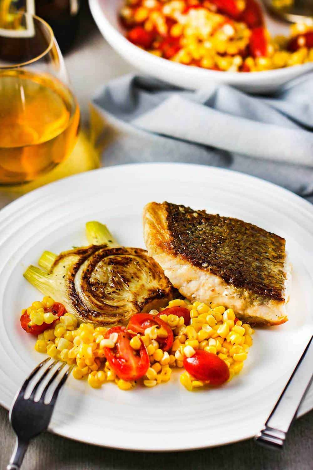 A white plate of sautéed wild striped bass with corn tomato salad and fennel