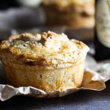 A Guinness beef pie sitting next to a bottle of Guinness beer.