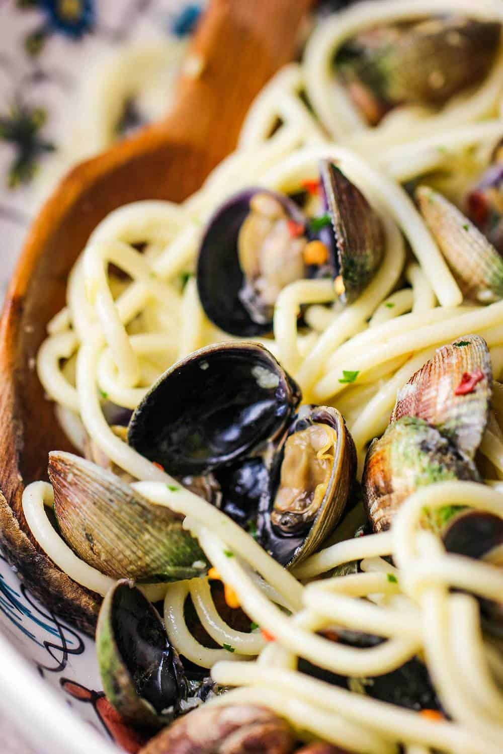 A close up view of cooked spaghetti vongole in a past bowl.