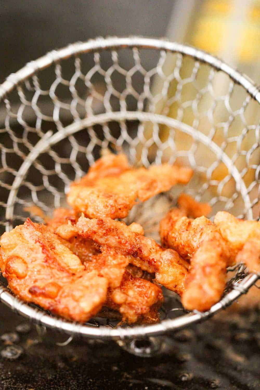 Deep fried pork strips in a metal spatula for Sweet and Sour Pork.