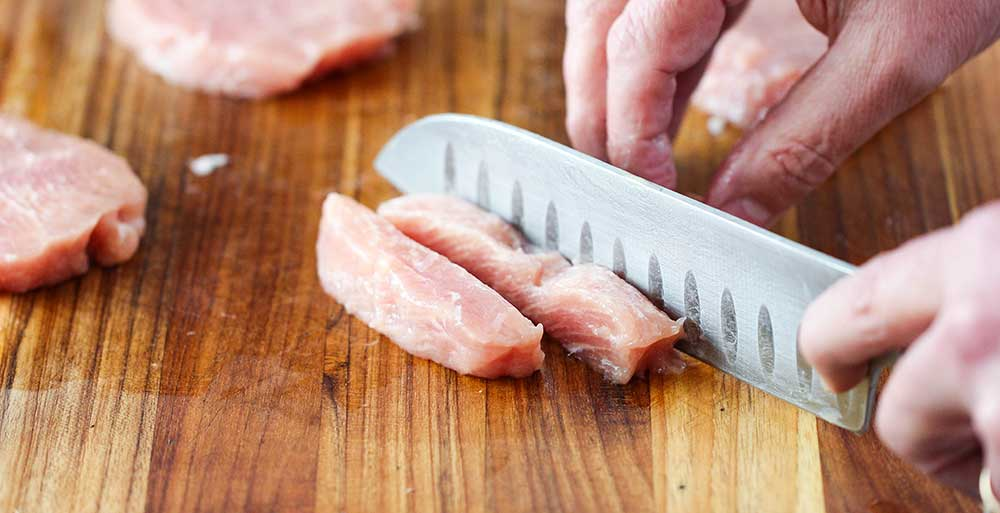 A hand and knife cutting a pork tenderloin into strips for Sweet and Sour Pork.