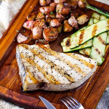 Grilled swordfish steaks on a cutting board