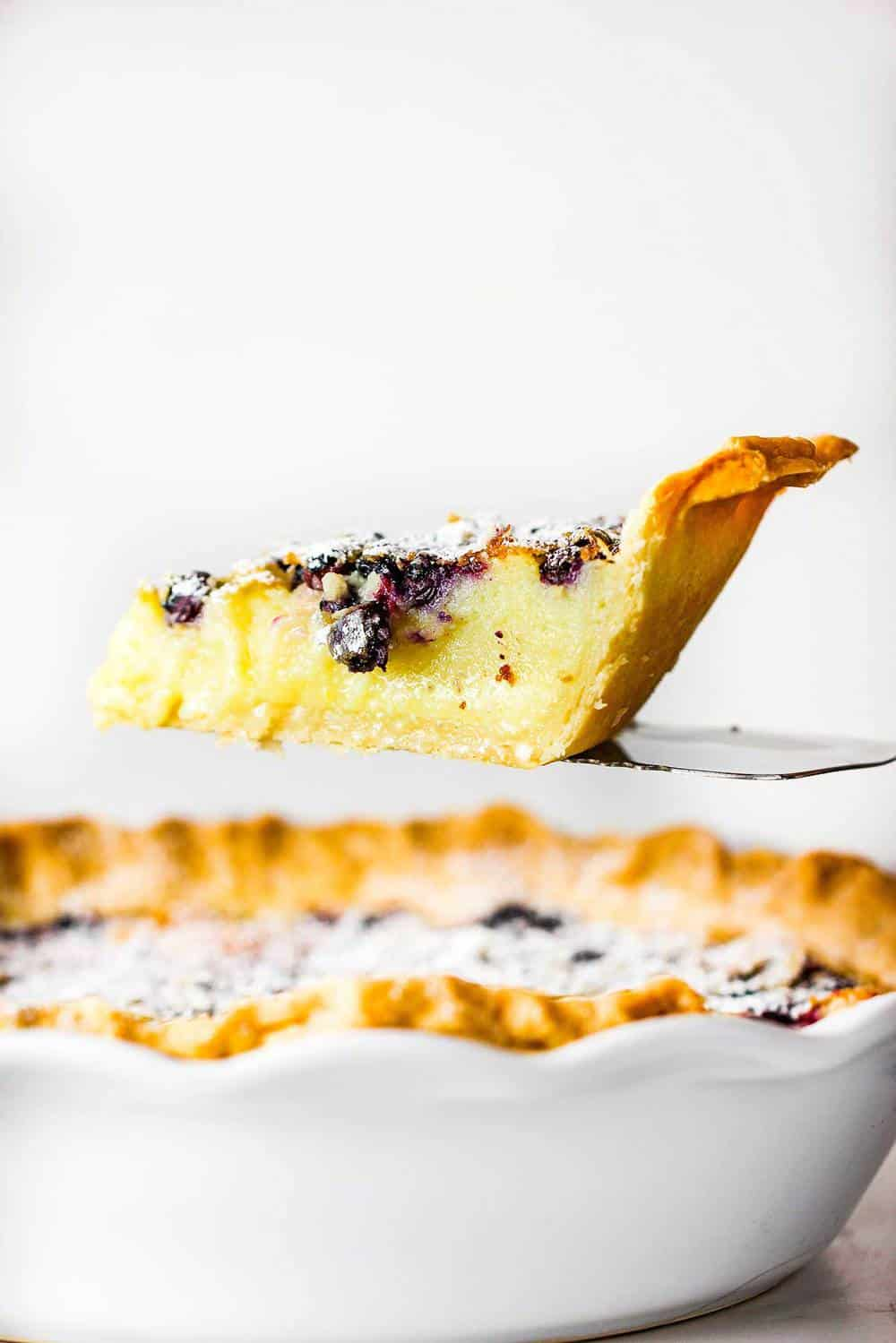 A slice of blueberry buttermilk pie being lifted from the pie on a spatula.