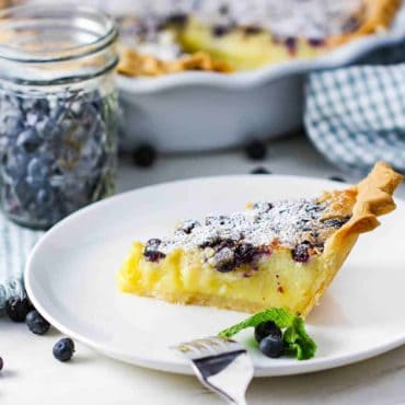 A slice of blueberry buttermilk pie on a white plate.