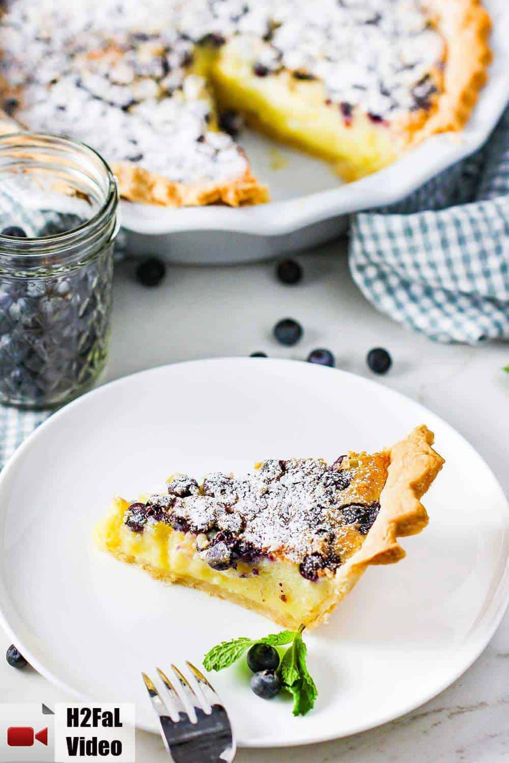A slice of blueberry buttermilk pie on a white plate