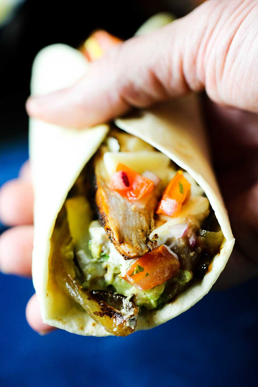 A rolled chicken fajita being held by a hand.
