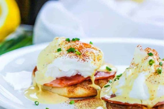 Classic eggs Benedict on a white plate next to cups of coffee and orange juice.