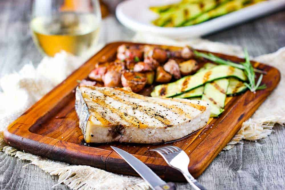 Grilled swordfish steaks on a cutting board with zucchini and baby potatoes