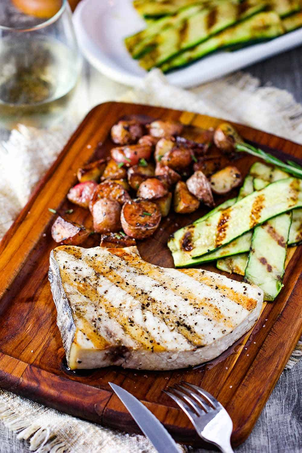 Grilled swordfish steak on a cutting board next to potatoes and grilled zucchini.