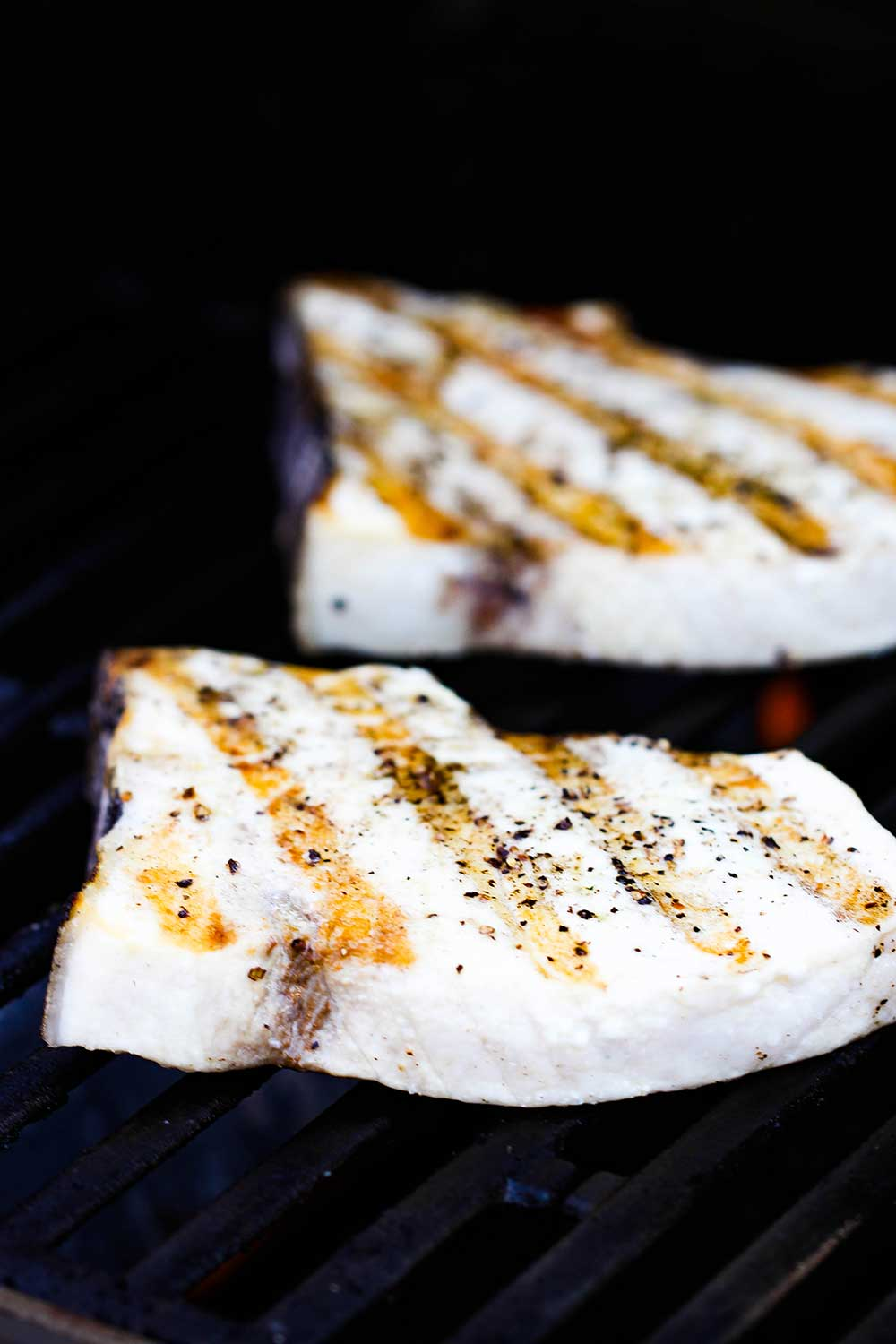 Two swordfish steaks on a hot grill.