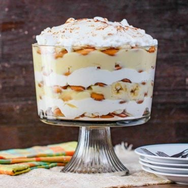 Banana Pudding next to a patterned napkin and a stack of white plates