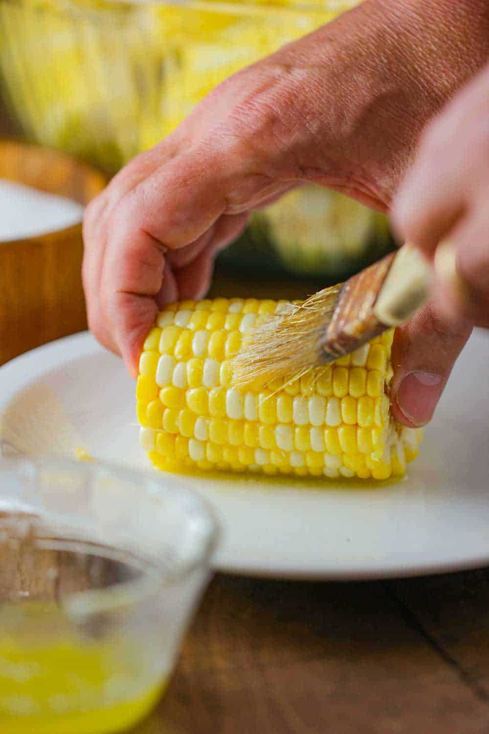 Brushing melted butter onto a corn niblet.