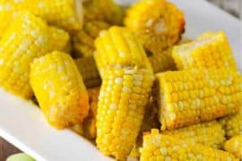 A white bowl holding slow-cooker corn on the cob.
