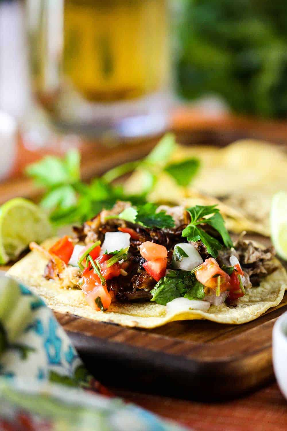 Pork carnitas tacos with traditional garnishes and a glass of beer.