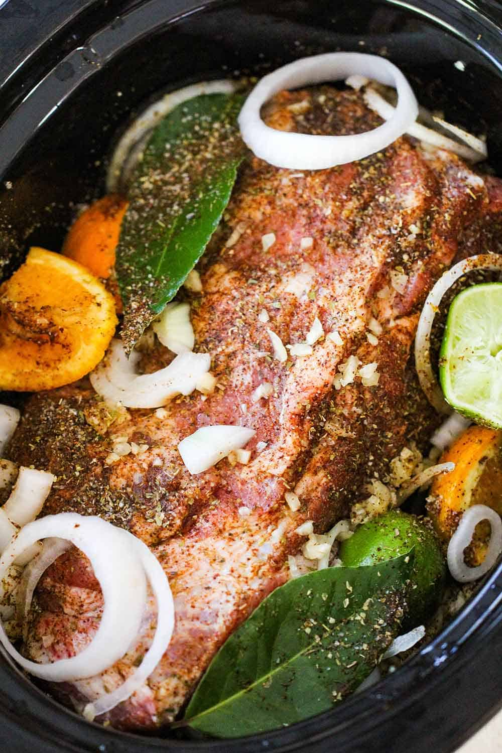 Place the pork shoulder into the slow cooker with aromatics, citrus and liquids.