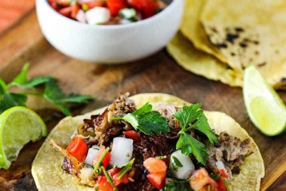Place the shredded pork carnitas on a corn tortilla with pico de Gallo, cilantro and fresh lime.