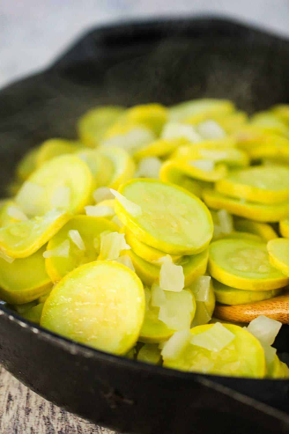 Yellow squash and chopped onion cooking in a large black cast iron skillet.