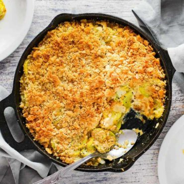 An overhead view of yellow squash casserole in a large black cast iron skillet.
