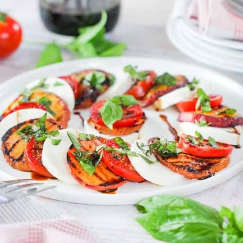 Caprese Salad with Grilled Peaches on a circular white platter.