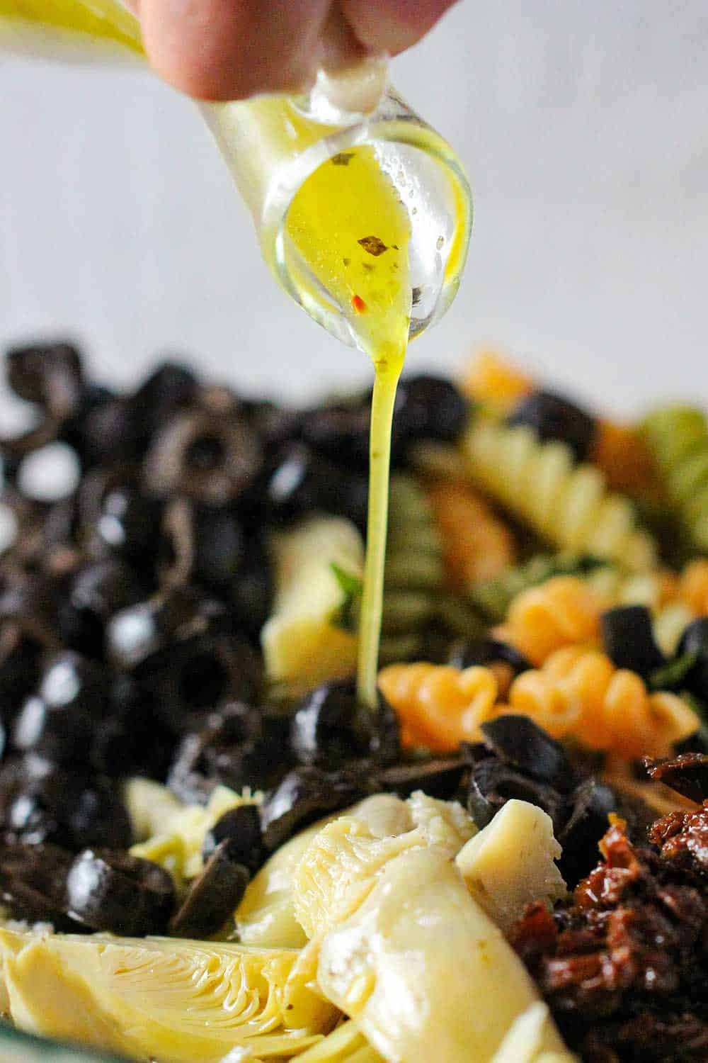 Italian dressing being pour onto a pasta salad with artichokes and black olives.