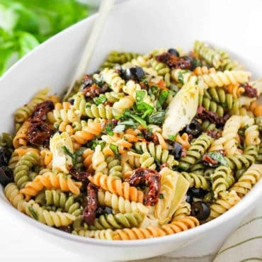 A white bowl containing fresh classic pasta salad.