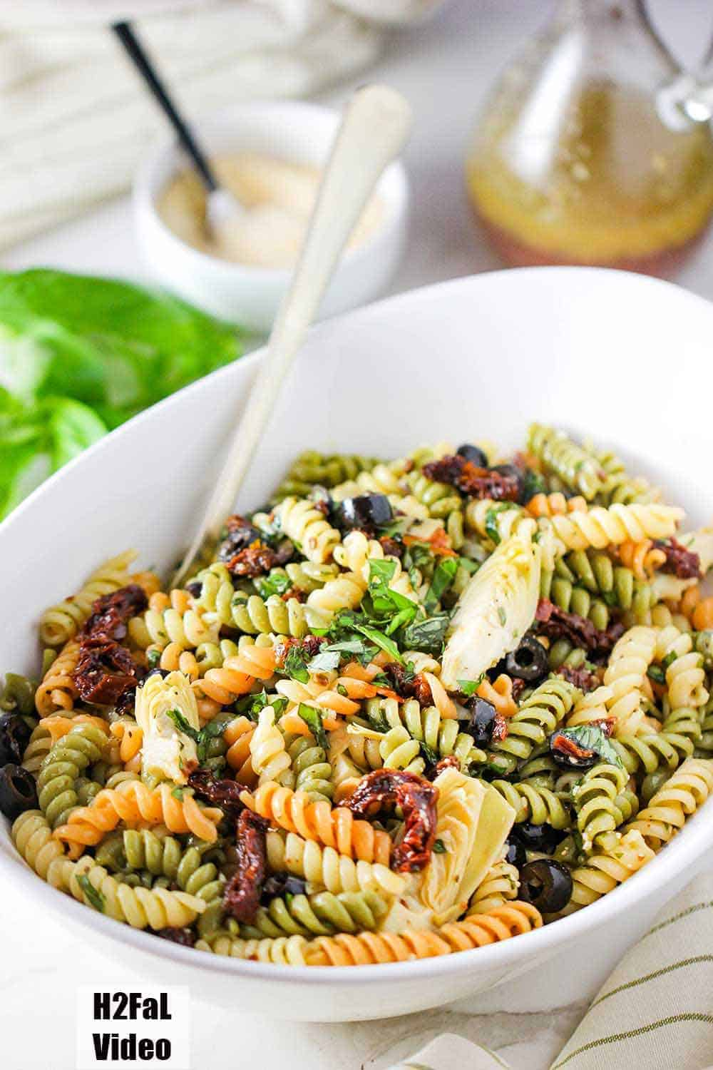 Classic Pasta Salad in a large white serving bowl with dressing and cheese nearby.