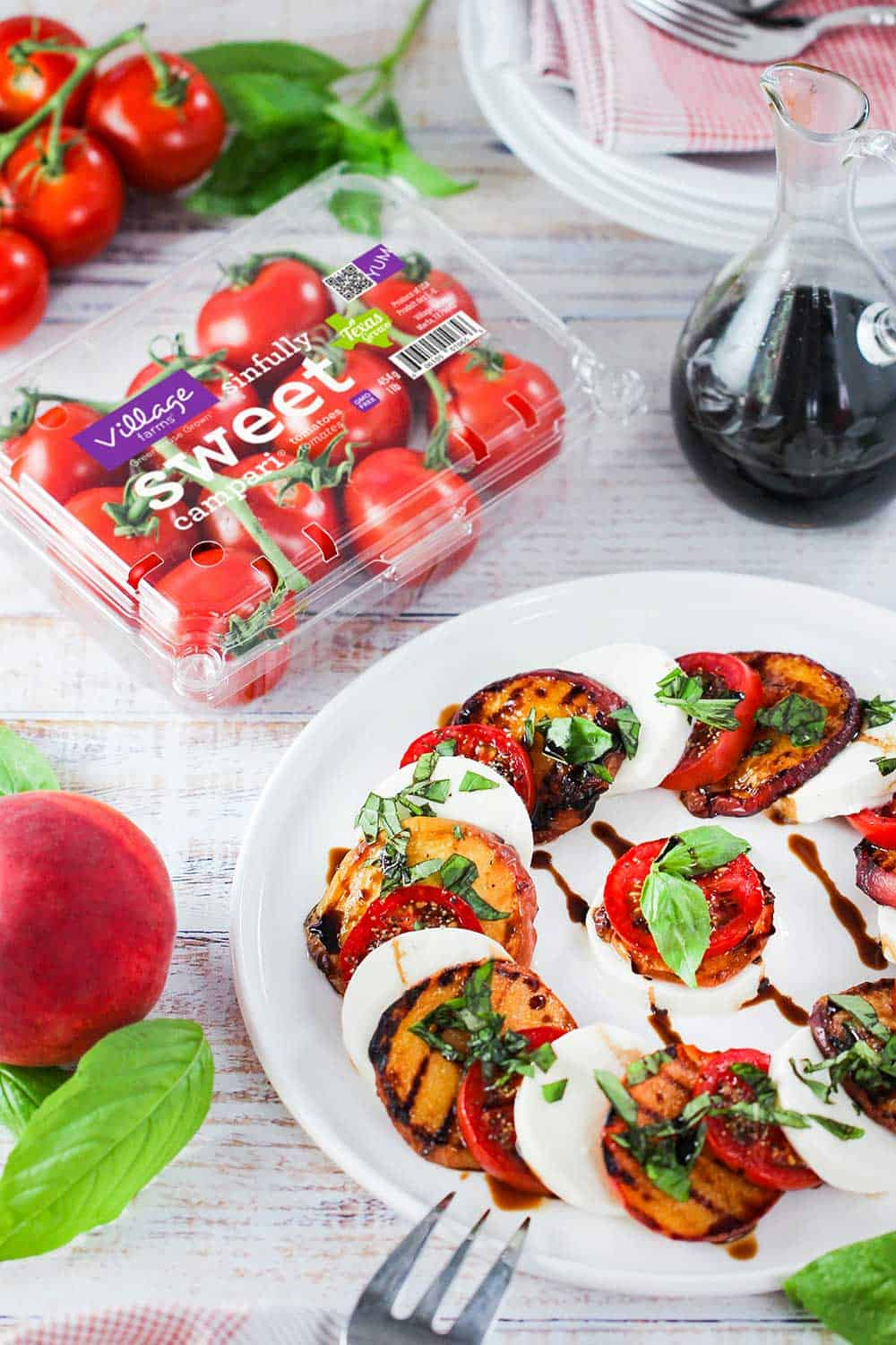 Caprese salad with grilled peaches on a white plate next to a package of campari tomatoes.