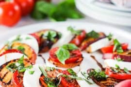 Caprese salad with grilled peaches on a white circular dish.