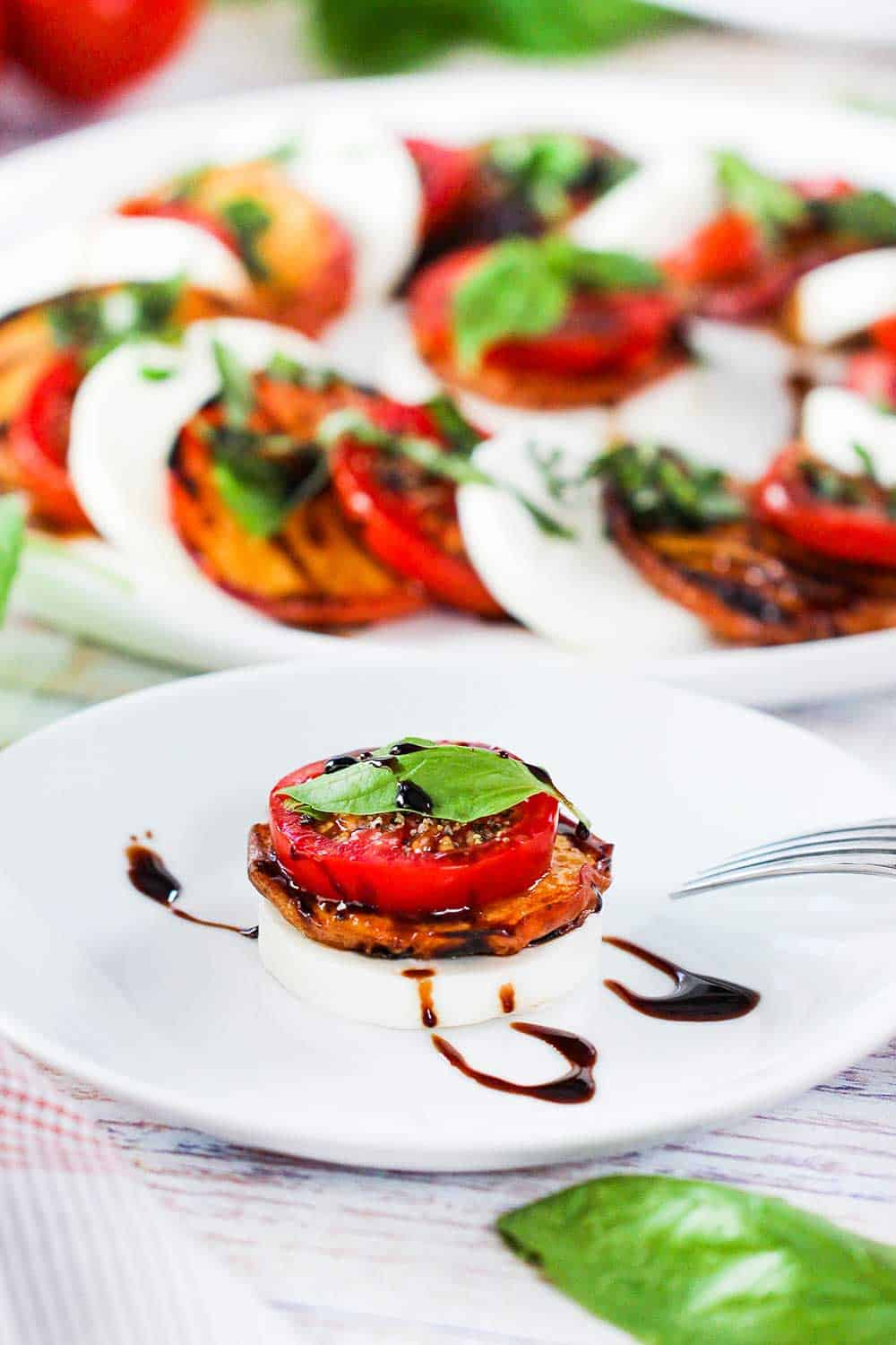 A single serving of caprese salad with grilled peaches on a white cocktail plate.