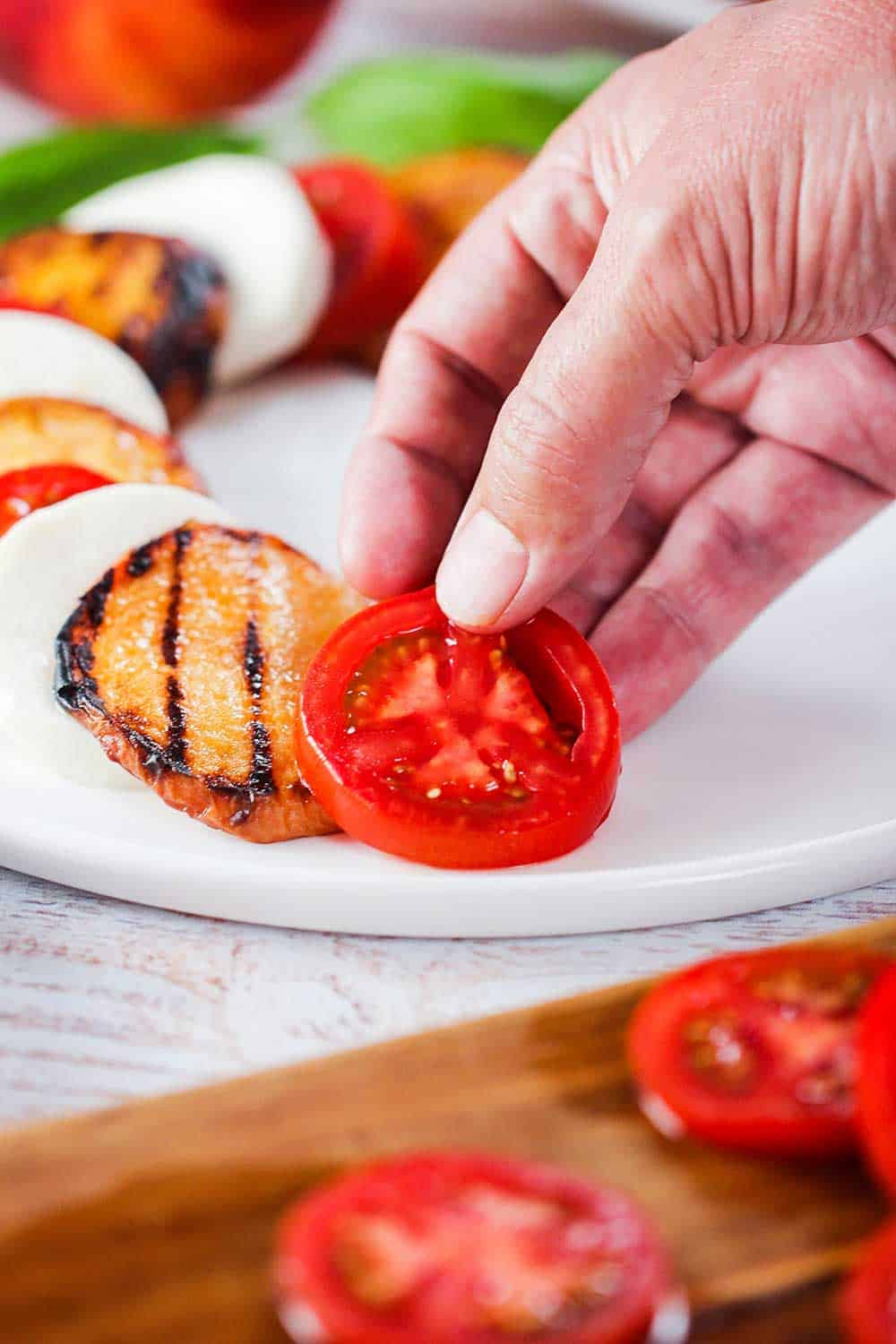 A hand layering a tomato for caprese salad with grilled peaches on a white plate.