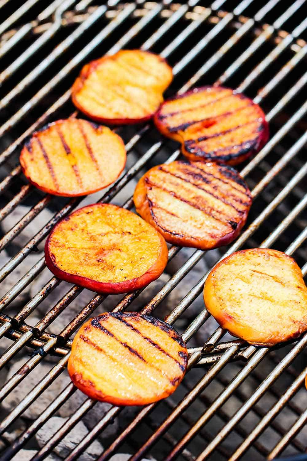 Sliced peaches on a charcoal grill