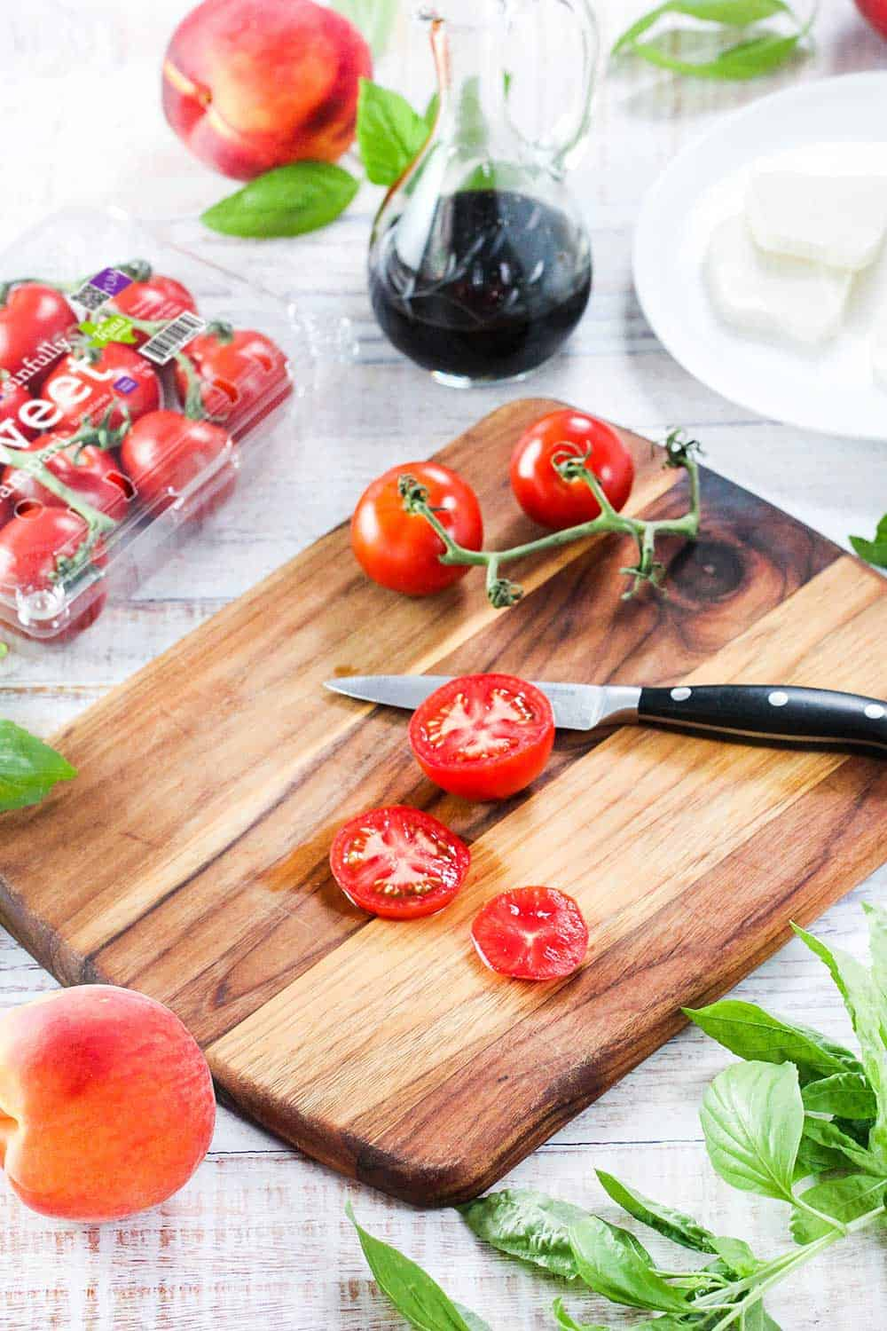Sliced compari tomatoes on a wooden cutting board with basil nearby.