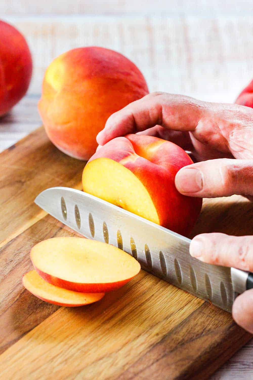 A chef's knife slicing through a yellow peach.