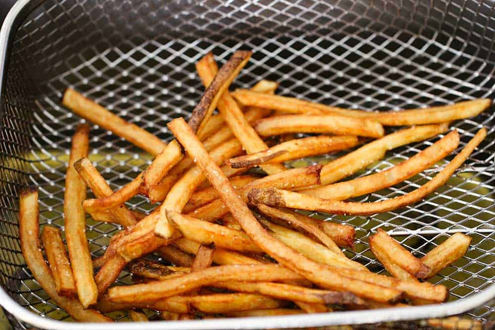 Homemade French fries in a basket of a deep fryer.