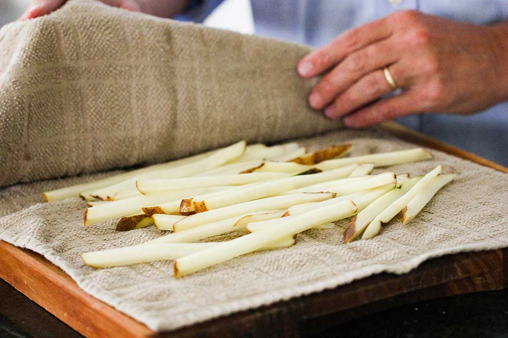 Two hands pressing a towel over cut potatoes for homemade French fries.