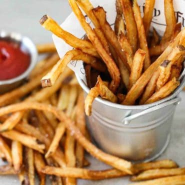 A small silver pale holding homemade French fries with a small bowl of ketchup nearby.