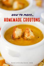 A white crock holding butternut squash soup with two homemade croutons on top.