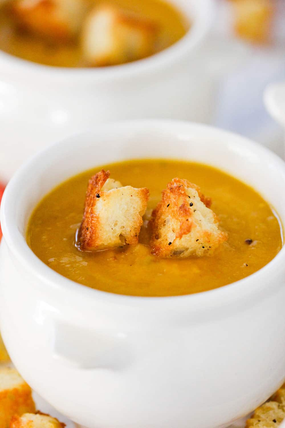 A white crock holding a bowl of butternut squash soup with two croutons on top.