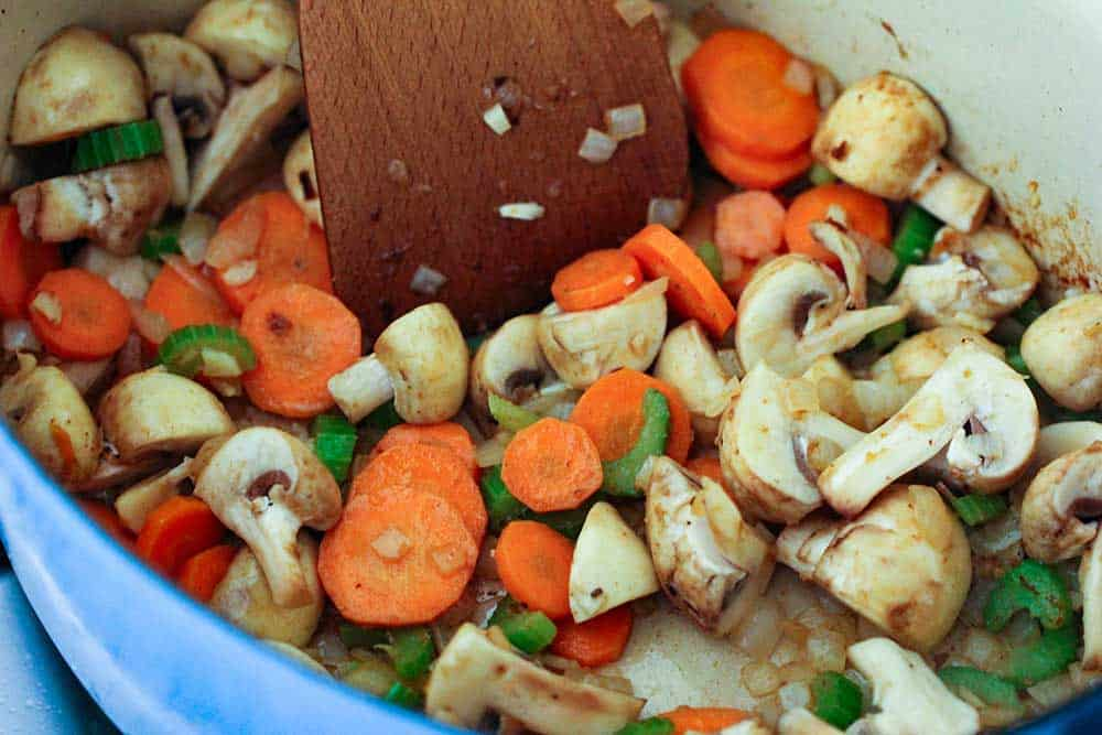 A wooden spoon moving around sautéed vegetables and mushrooms in a blue Dutch oven.