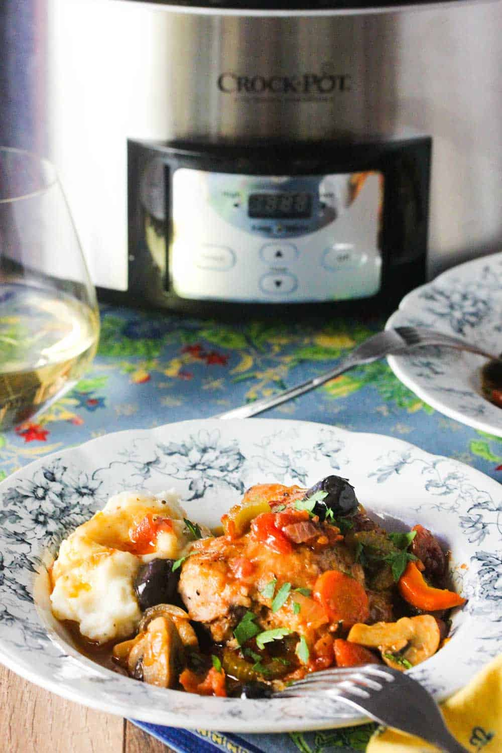 A small bowl of Provençal Chicken Stew in front of a stainless steel Crock-Pot.