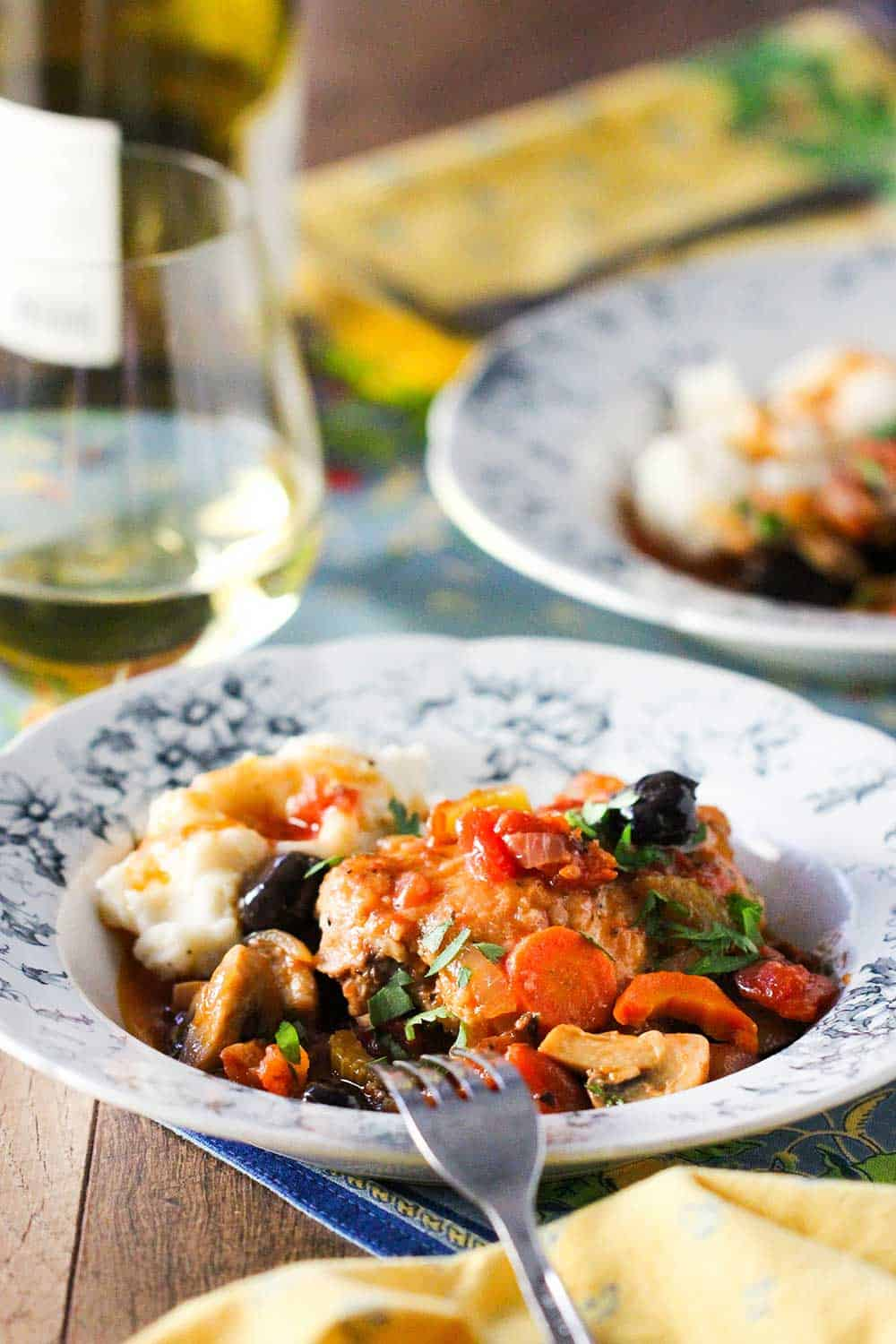 A French dish filled with seared chicken with a tomato, mushrooms and vegetables with a bottle of white wine next to it.